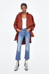 fundo branco, uma mulher negra em pé com as mãos no bolso. Ela usa uma blusa branca e um casaco longo vermelho terroso e uma calça jeans. a calça é azul clara e vai até a altura das canelas. Na altura da virilha, logo abaixo dos bolsos, há uma variação no tom de azul, entre mais escuro e mais claro, junto às dobras do jeans.