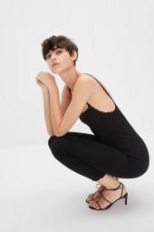 fundo branco, mulher branca de cabelo curto agachada, visão de perfil. Ela usa uma leging preta num look minimalista composto por regata de alxinha preta e sandalha preta de tirinhas e salto alto