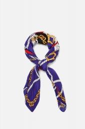 fundo branco, lenço em círculo, amarrado com um nó. a estampa tem um fundo azul anil com desenhos de cordas brancas e correntes douradas. o tecido é plissado.